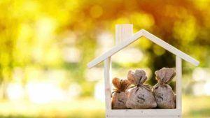 Gebasteltes Holzhaus mit kleinen Geldsäckchen