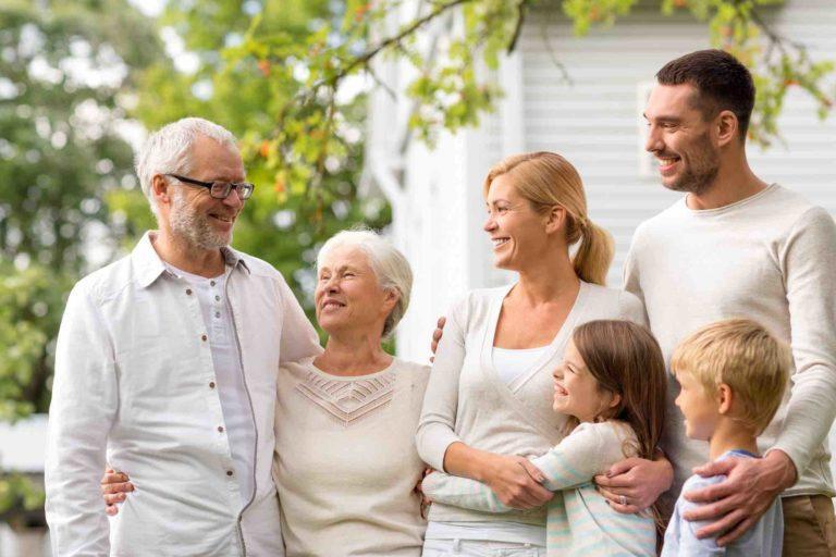 3 Generationen Familie steht vorm Haus