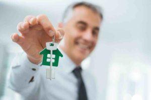 Mann hält Schlüssel für ein Haus in der Hand