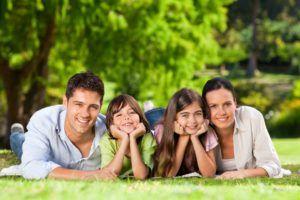 Eltern liegen gemeinsam mit Tochter und Sohn auf einer Wiese