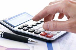 Mann tippt in Taschenrechner seine Steuer ein