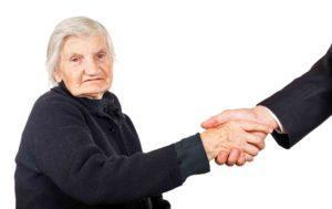 Alte Frau reicht einem Mann ihre Hand