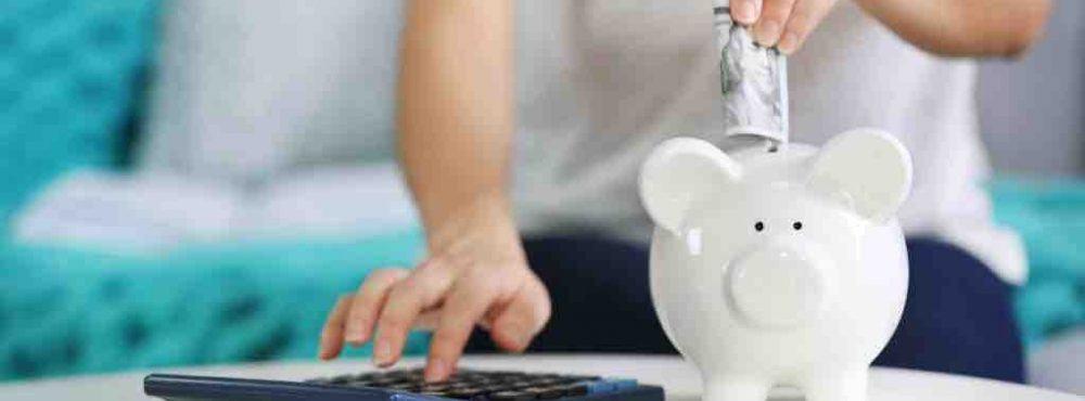 Frau steckt einen Geldschein in ein Sparschwein