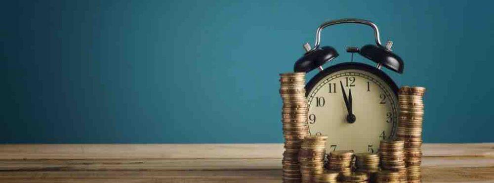 Wecker als Symbol für Zeit und mehrere Stapel mit Münzgeld