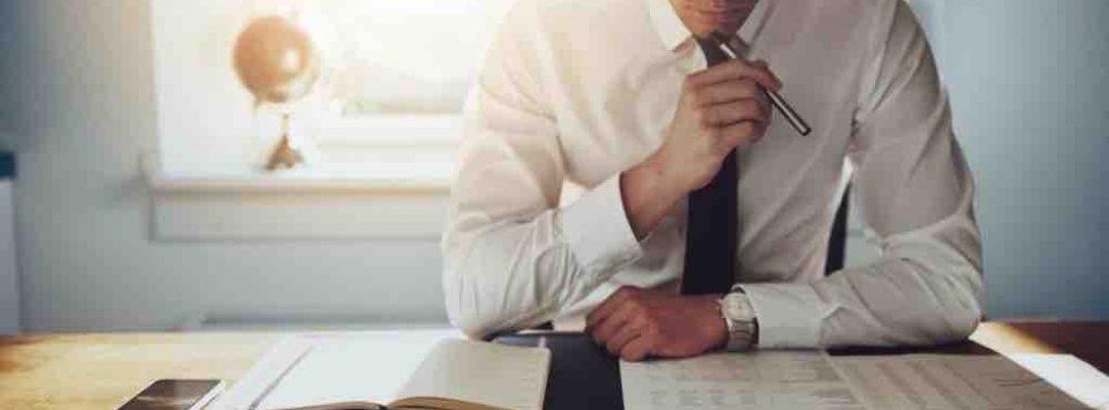 Mann grübelt über Dokumenten