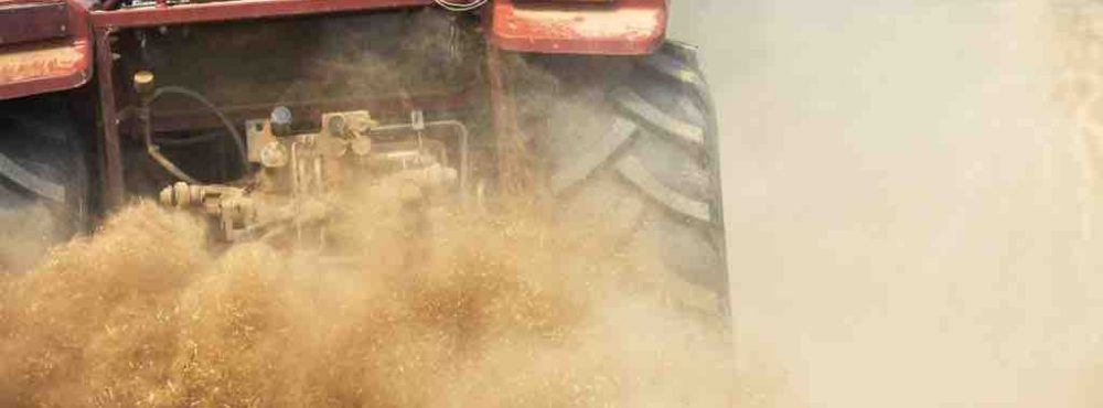 Traktor fährt über Feld und wirbelt Staub auf